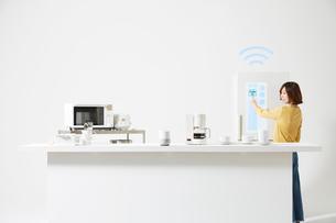 冷蔵庫を操作する女性の写真素材 [FYI02466442]