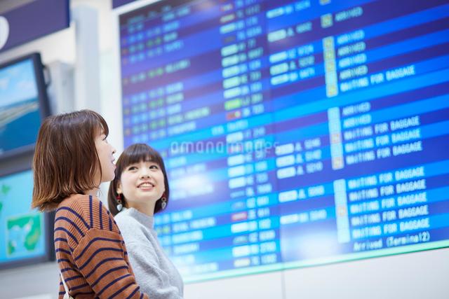 空港の電光掲示板を見ている二人の女性の写真素材 [FYI02466449]