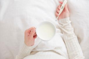 ベッドの上でホットミルクのカップと体温計を持つ女性の手元の写真素材 [FYI02466475]