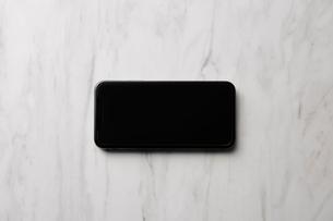 大理石天板の上に置かれたスマートフォンの写真素材 [FYI02466552]