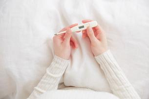 ベッドの上で体温計持つ女性の手元の写真素材 [FYI02466556]