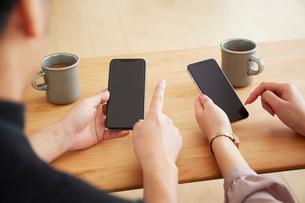 スマートフォンを持つ2人の男女の写真素材 [FYI02466565]
