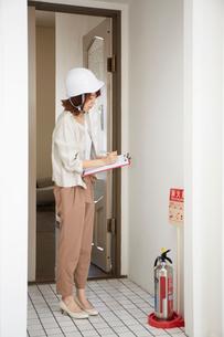 ヘルメットを被り書類を持ちながら点検をする女性の写真素材 [FYI02466578]