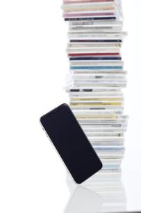 新しいスマートフォンと背景に積み上げられたCDケースの写真素材 [FYI02466606]