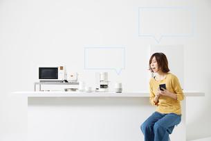 スマートスピーカーで家電を操作する女性の写真素材 [FYI02466642]