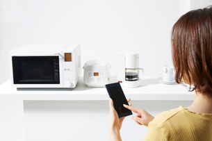 キッチンでスマートフォンを操作する女性の写真素材 [FYI02466681]