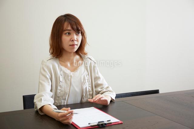 デスクで書類とペンを持つ女性の写真素材 [FYI02466682]