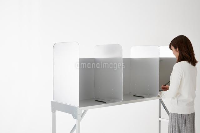 投票記載台を使用している女性の写真素材 [FYI02466749]