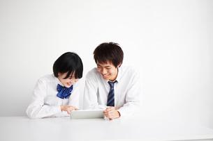 机の上でタブレットを見る男子高生と女子高生の写真素材 [FYI02466800]
