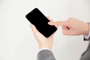 スマートフォンを操作するサラリーマンの手元の写真素材 [FYI02466864]