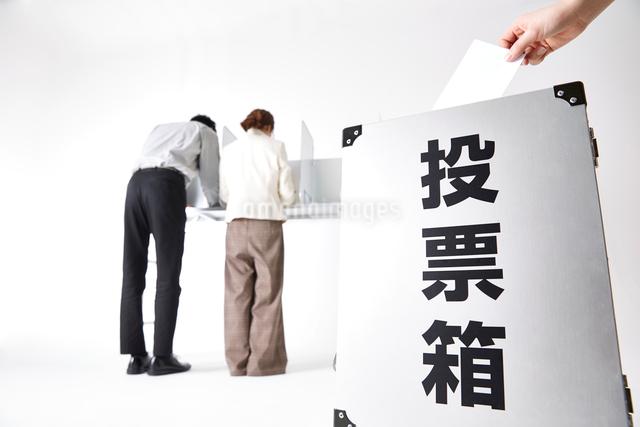 投票箱に投票する人の手と記載台で記入する人々の写真素材 [FYI02468785]
