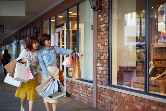 買い物をして歩く二人の女性の写真素材 [FYI02468786]