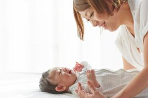 白いシーツの上で寝ている赤ちゃんとお母さんの写真素材 [FYI02468787]