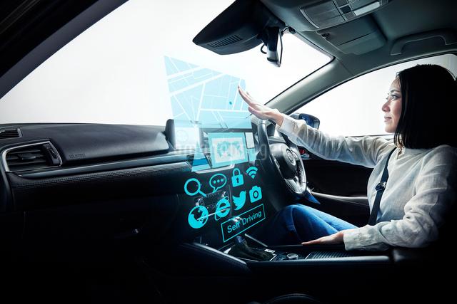 自動運転車に乗る女性の写真素材 [FYI02469014]