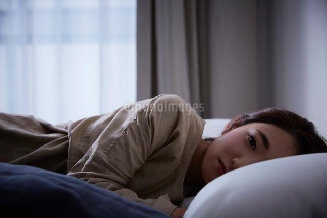ベットに寝転んでカメラ目線をする暗い表情の女性の写真素材 [FYI02469100]