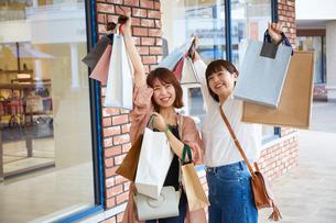 買い物をしたショッピングバックを見せる二人の女性の写真素材 [FYI02469116]