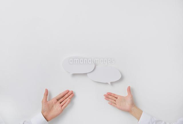 意見交換を表現した吹き出しと男女の手の写真素材 [FYI02469141]