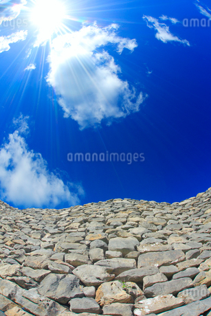 今帰仁城跡の城壁と太陽の光芒の写真素材 [FYI02470197]