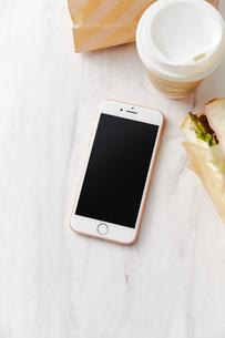 大理石天板の上に置かれたコーヒーとスマートフォンの写真素材 [FYI02470225]