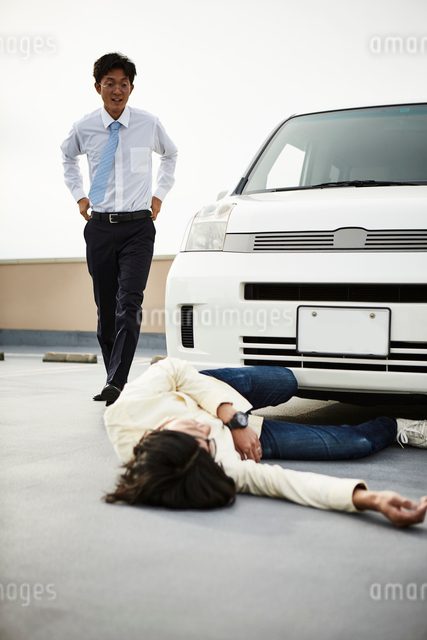 車の前に倒れている男性とそこに駆け寄る男性の写真素材 [FYI02470337]