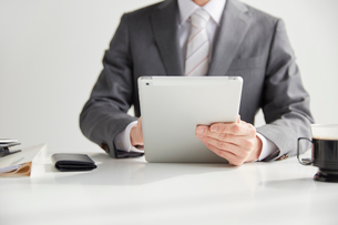 机の前に座ってタブレットを持つサラリーマンの写真素材 [FYI02470408]