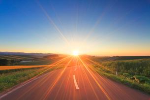 パッチワークの路と夕日の光芒の写真素材 [FYI02470472]