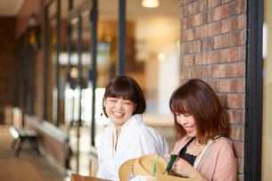 たくさん買い物をしてベンチに座る女性の写真素材 [FYI02470582]