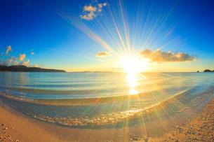 奥間ビーチの渚に打ち寄せる波と夕日の写真素材 [FYI02470691]