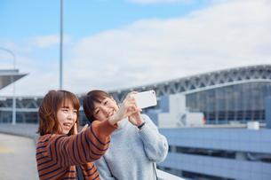 空港でスマートフォンで自撮りをする二人の女性の写真素材 [FYI02470693]
