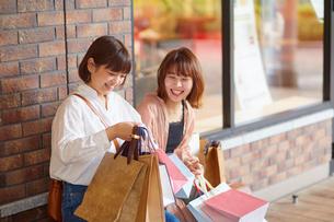 たくさん買い物をしてベンチに座る女性の写真素材 [FYI02471147]