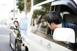 2台の車の窓から顔を出す二人の男性の写真素材 [FYI02471377]