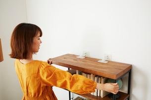 本棚に転倒防止グッズをつけている女性の写真素材 [FYI02471429]