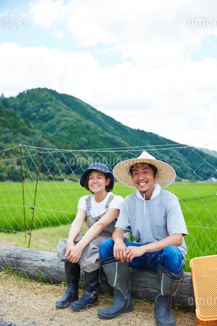 水田の前で丸太に腰掛ける笑顔の男女の写真素材 [FYI02471441]