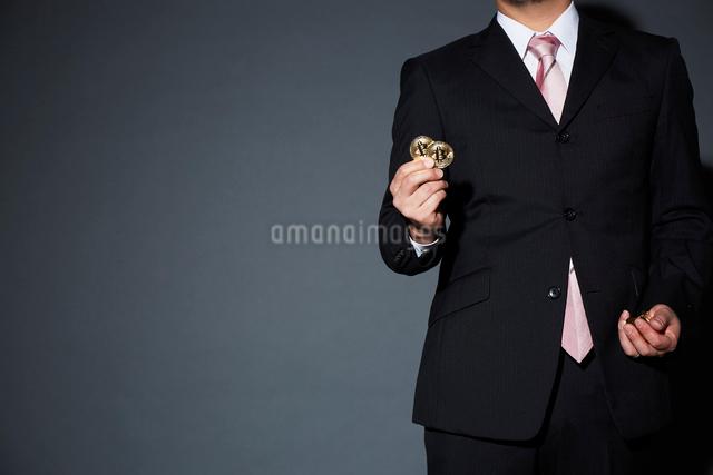 ビットコインを持ったスーツを着た男性の写真素材 [FYI02471442]