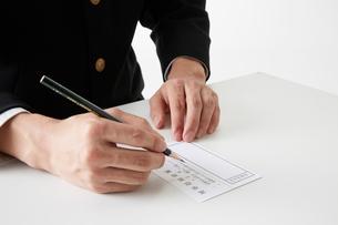 投票用紙に記入する男子学生の手元の写真素材 [FYI02472983]