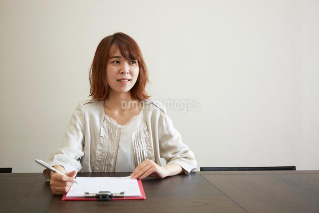 デスクで書類とペンを持つ女性の写真素材 [FYI02473063]