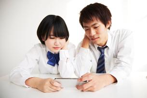 机の上で肘をついてスマートフォンを見る男子高生と女子高生の写真素材 [FYI02474310]