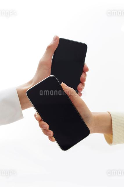 新しいスマートフォンを持つ二人の手の写真素材 [FYI02474334]