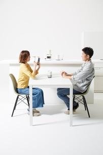 AIスピーカーが置いてあるダイニングで会話する男女の写真素材 [FYI02474409]