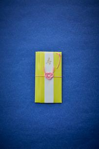 青い天板の上に置かれた黄色いご祝儀袋の写真素材 [FYI02474498]