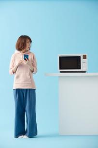 電子レンジをスマートフォンで操作する女性の写真素材 [FYI02474601]