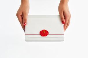 水引の飾りが付いたギフトボックスを持つ女性の写真素材 [FYI02474669]