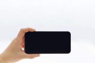 新しいスマートフォンを横向きで持つ人の写真素材 [FYI02474717]