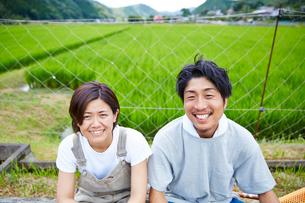 水田の前で笑う男女の写真素材 [FYI02474762]