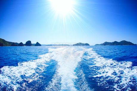 航跡と太陽の光芒と嘉比島など慶良間諸島の写真素材 [FYI02475274]