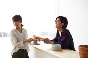 料理が盛られたお皿を受け渡しする2人の女性の写真素材 [FYI02475951]