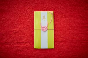 赤い天板の上に置かれた黄色いご祝儀袋の写真素材 [FYI02476165]