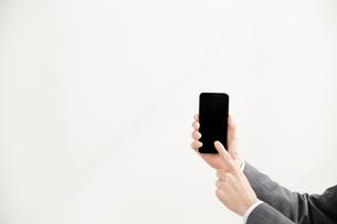 スマートフォンを操作するサラリーマンの手元の写真素材 [FYI02477324]