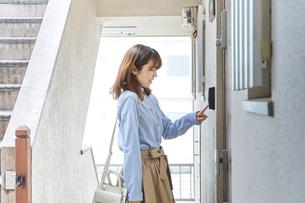 マンションのドア前でインターフォンをならす女性の写真素材 [FYI02477327]