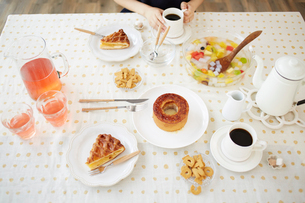 お菓子が並べられたテーブルとコーヒーを飲む女性の写真素材 [FYI02477333]